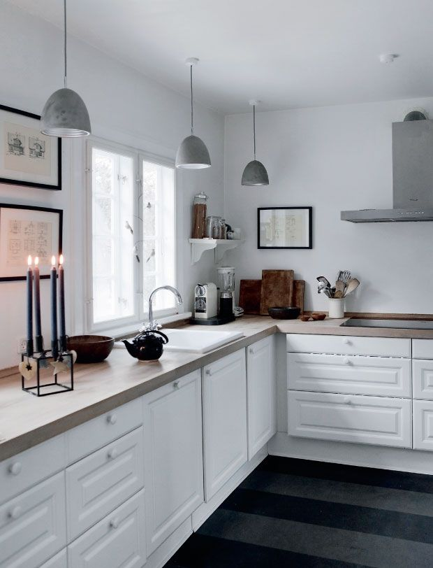 white kitchen with no upper cabinets, art and a couple ledges instead