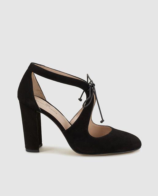 Zapatos de tacón elaborados en piel de color negro, con puntera redonda y cierre de cordones sobre la pala. Tacones forrado al tono de caucho y con  8 cm de altura.