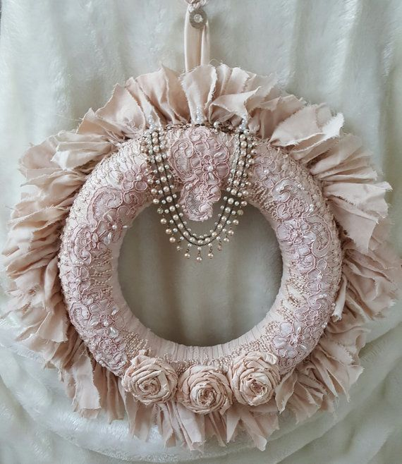 This is a shabby chic wreath.Here I have covered a flat-backed Styrofoam wreath with cotton fabric.I have then added lots of wedding appliques