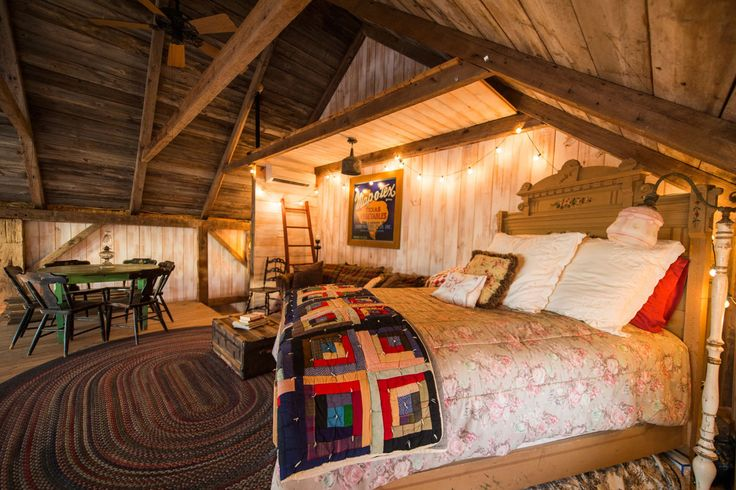 Quilts, string lights, and vintage furniture lends character to the cozy bedroom.   - CountryLiving.com