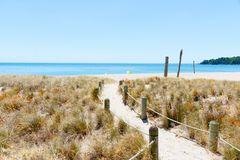 Monte la playa del océano en la trayectoria caliente de la arena del día de verano que lleva al mar Imagen de archivo libre de regalías