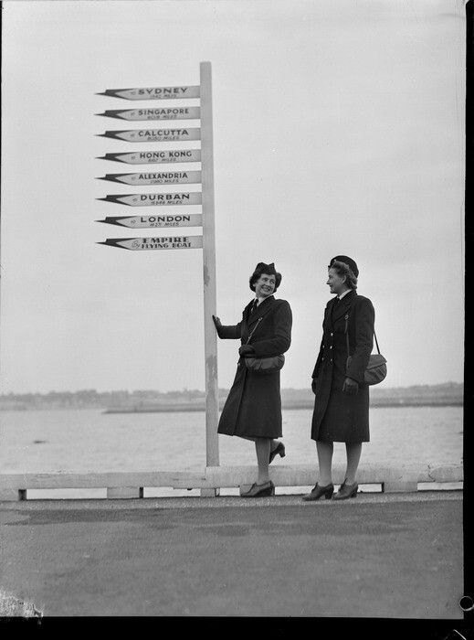 Portrait of Miss B P Morton and Miss L M Magnus, TEAL Stewardesses in uniform with wharf signpost, Mechanic's Bay, Auckland. Date: 13 Aug 1946. Photograph taken by Whites Aviation.