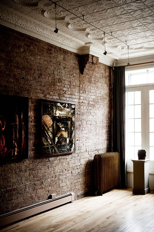 Bare brick walls and detailed antique moulded plaster ceiling with modern art in this lofty space