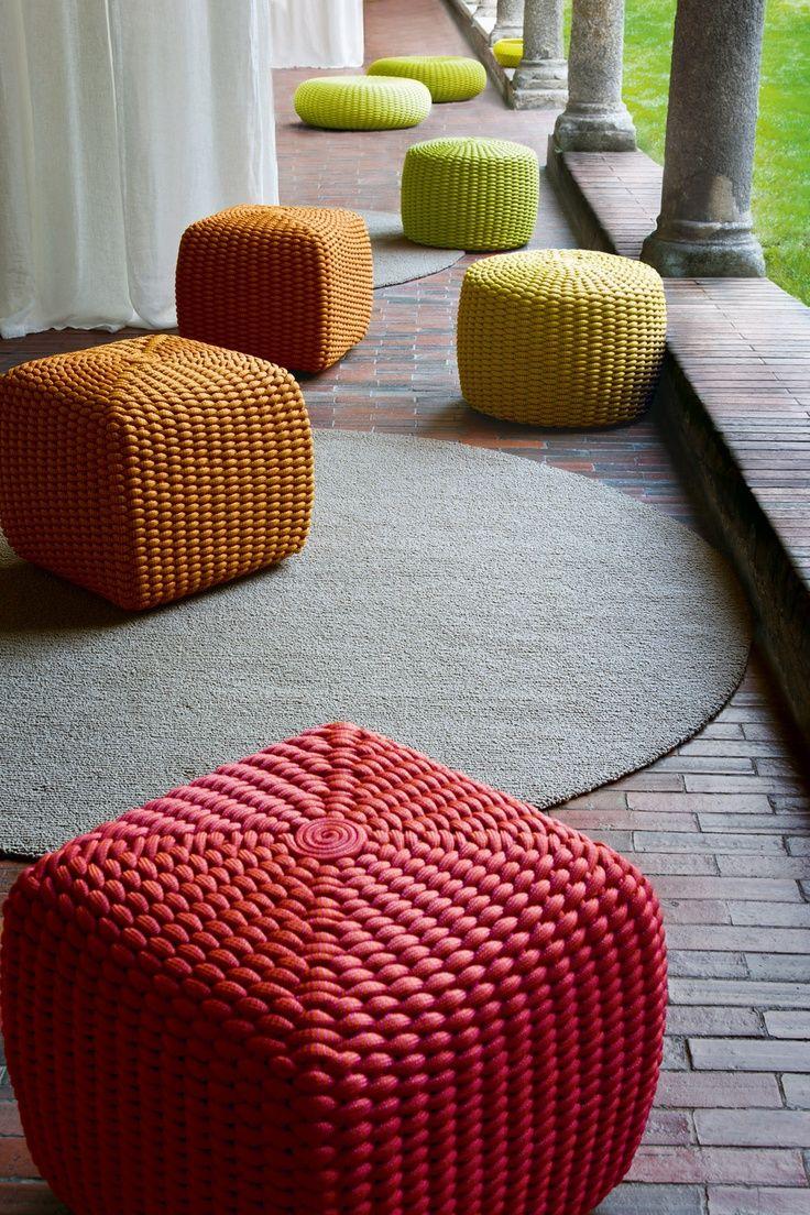 Colorful woven ottomans on veranda.