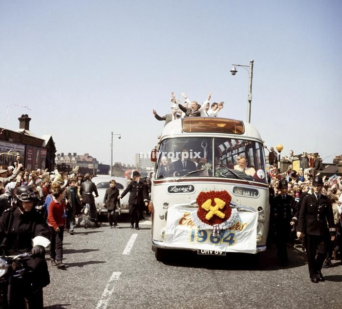 West Ham United captain holds aloft the FA Cup from an open top double decker bus as the team parades the trophy through the streets of East London after their victory in the Cup Final May 1964