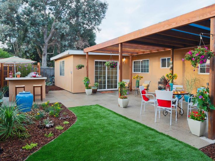 This backyard makeover from DIYNetwork's Yard Crashers is a multi-purpose space with a wooden pergola covering an entertaining space with a retro metal dining set. Further in to the yard, a custom bar with wooden bar stools overloooks a water feature and small garden bed.