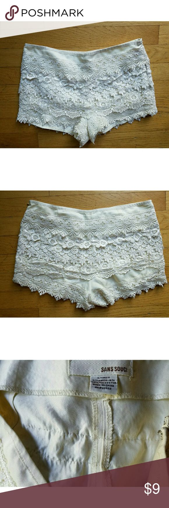 Dressy Sans Souci Ivory Lace Shorts Small Dress up your game with this preowned pair of Dressy Sans Souci Ivory Lace Shorts womens small. Polyester lace shell fully lined with a poly short. Concealed side zipper. In very good condition! Sans Souci Shorts