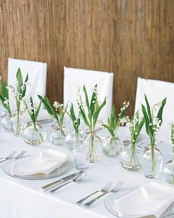 For a modern look, a whimsical row of lily of the valley in a variety of glass bud vases makes a charming -- and cost-effective -- centerpiece for a long reception table. The clear glass tumblers and dinnerware and crisp white linens complete the spare setting.