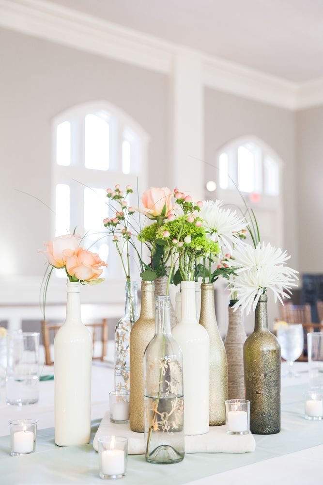 Wine bottle centerpieces painted in gold or white with an assortment of flowers.  Jessica's & Josh's Savannah wedding at Forsyth Park. Photographed by Priscilla Thomas Photography.
