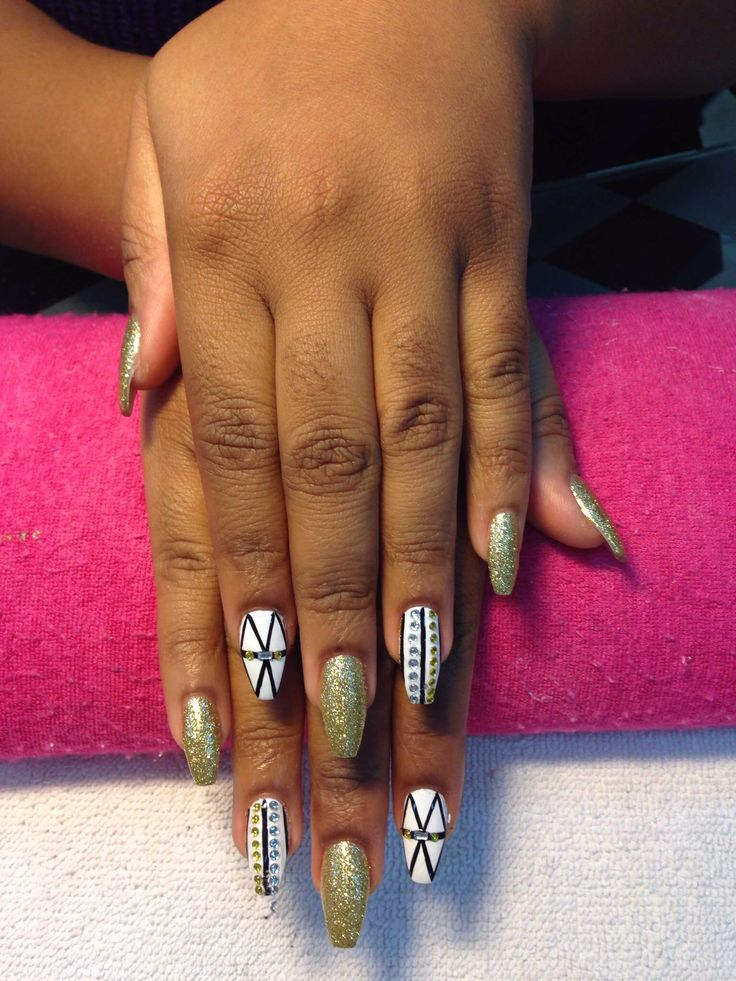 Squared stiletto nails with gold, white and black designs, coffin nail