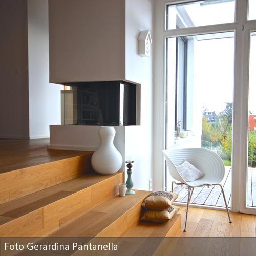 Die Zwischenebene ist eine Verlängerung des Flurs und verbindet die Küche mit dem Wohn/Essbereich. Der gläserne Gaskamin ist dabei der Blickfang