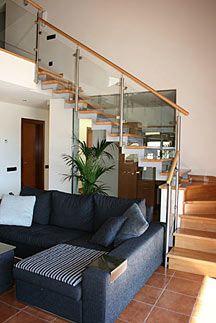 escalera estructura metal con barandilla de cristal y pasamanos de madera