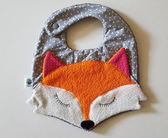Bib melirenard accessory that fits your baby with humor and tenderness. Ideal gift for a birth. From little Fox head of an original personal illustration.  Size 6-24 months. Terry and gray and white geometric print. The little fox ears are highlighted with pink polka dots. Side snap
