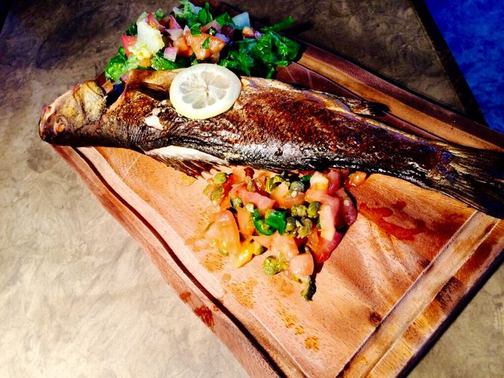 Fresh fish on the BBQ. Sea Bass Stuffed with fresh herbs and garlic butter and grilled to perfection over hot coals