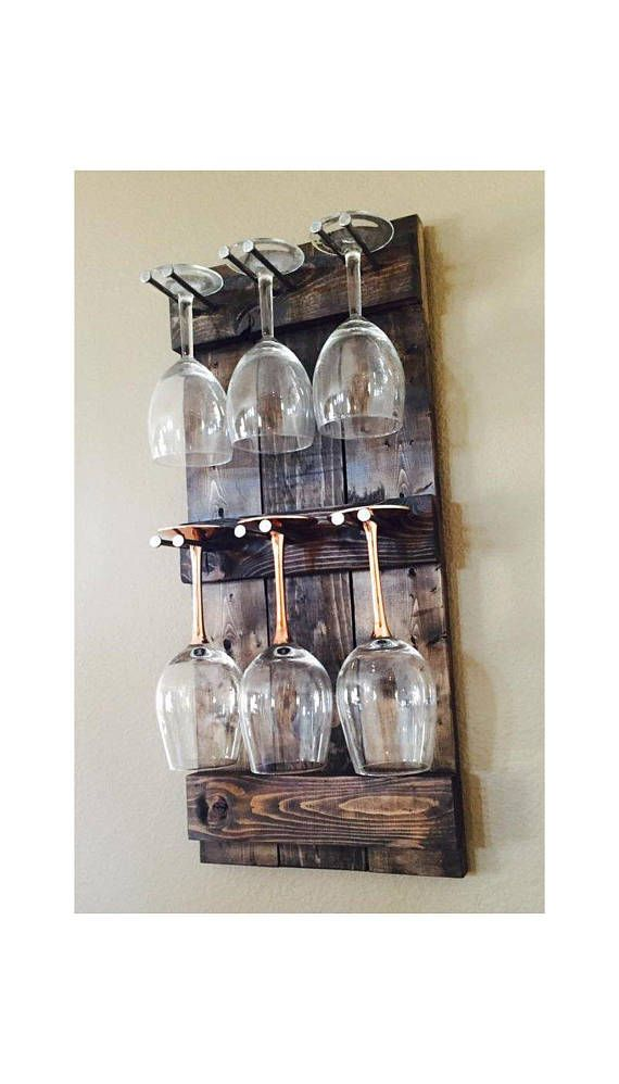 This rustic wine glass rack holds 6 large wine glasses. It is custom-made to order in any stain or paint color. It is made of reclaimed pine. The pegs that hold the wine are steal spikes. This is a great piece to display your wine glasses in the kitchen or behind the bar.