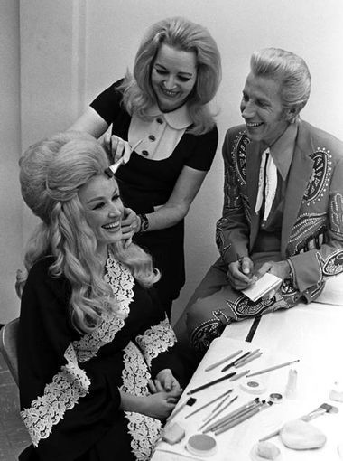 "Porter Wagoner, right, and Dolly Parton, left, discuss an upcoming episode before taping of his half-hour syndicated television show, ""The Porter Wagoner Show,"" at the WSM-TV studios in Nashville. Jo Coulter, center, puts finishing touches on Parton's makeup in the dressing room."