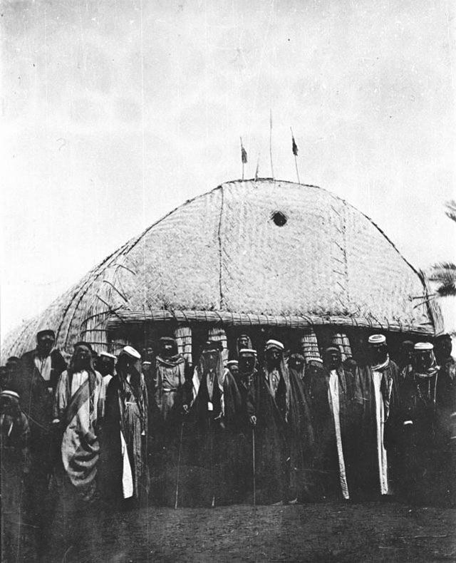 1918, Gertrude Bell photo, Iraq, ['Abdul Wahid and tribesmen standing outside reed building (mudhif)]