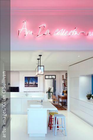 Die cleane Einbauküche in Weiß erstrahlt zusammen mit dem ebenso alpinweißen Fußboden. Die Leuchtschrift-Deko lockert die streng minimalistische Grundstimmung auf und gibt einen erfrischenden künstlerischen Touch.