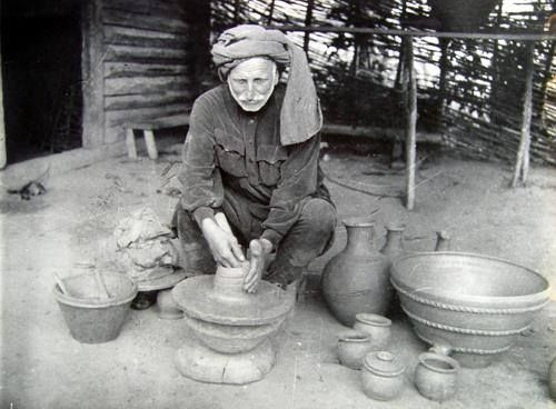Mingrelian old man is sculpturing vessel from clay.