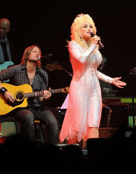 Keith Urban and Dolly Parton entertain the crowd during the We're All for the Hall benefit concert at Bridgestone Arena in Nashville.