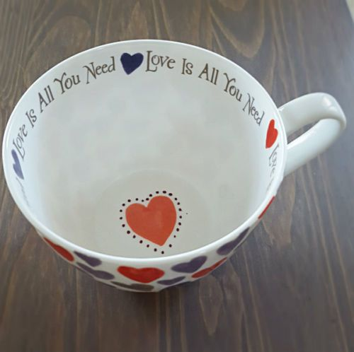 """Lots of Hearts cover this large Coffee or Tea mug with """"Love is all you Need"""" and hearts around interior rim and a fun red heart at the bottom of mug."""