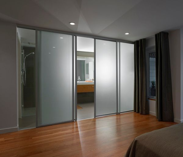 Frosted glass sliding doors separate the contemporary bedroom from the sleek bathroom