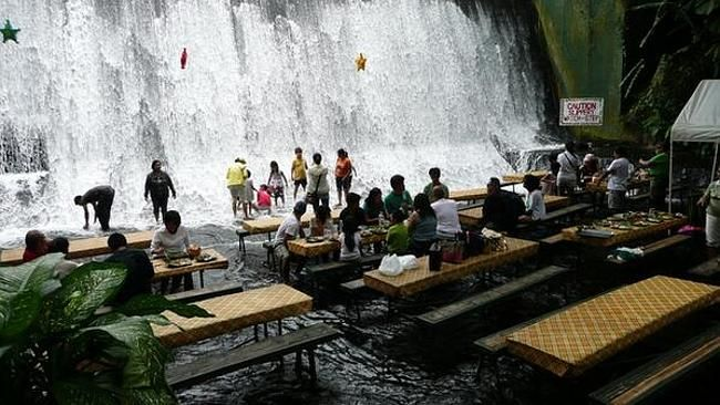 """SNAGGING the """"best seat in the house"""" at Villa Escudero's Waterfalls Restaurant also means you'll get completely soaked. The restaurant at this Philippines resort features bamboo tables set in the spillway of the Labasin Falls. Diners can nosh on a buffet of curries and meats while water rushes over their feet, taking breaks between bites to dunk in the running cascade. The restaurant at ..."""