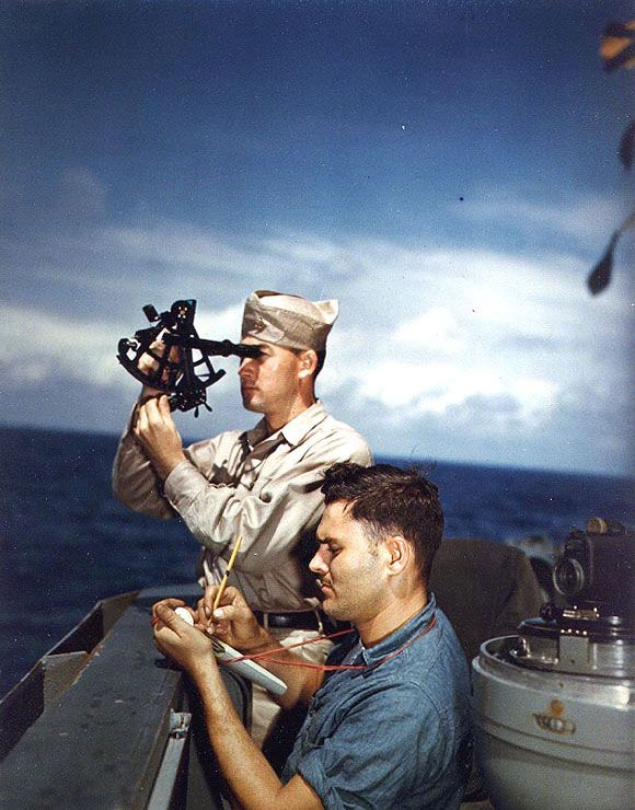 Battleship USS Alaska's Chief Quartermaster John P. Overholt took a sun sighting with a sextant, off Iwo Jima, 6 Mar 1945; taking notes on the observations was QM3/c Clark R. Bartholomew (US National Archives)