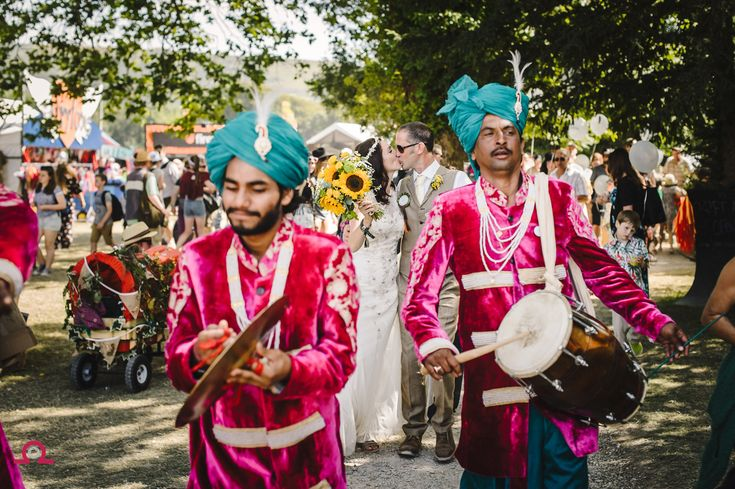 Can you have a wedding at a music festival? Yes, you can. Camp Bestival at Lulworth Castle is the perfect setting and it's fully legal! This photograph is after the ceremony while walking through the crowds, accompanied by a Bengali marching band. Epic! Libraphotographic.co.uk