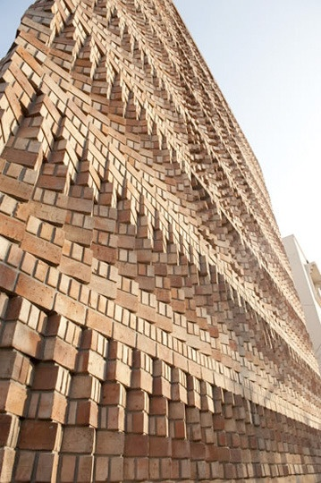 Beautiful brick facade shields the South Asian Human Rights Documentation Centre in India, doing double duty as a solar screen and noise buffer.