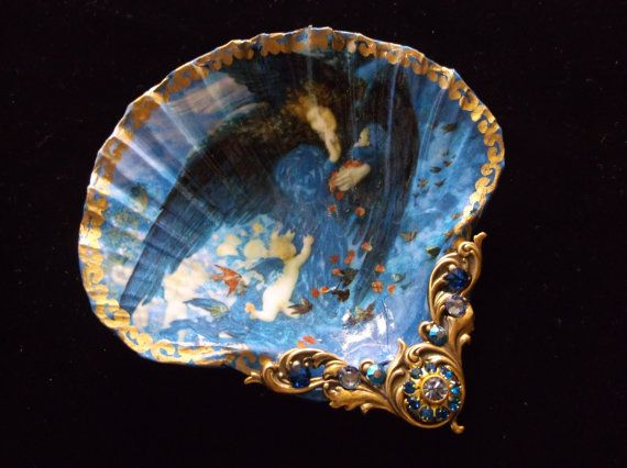 This sea shell has a classic painting called Night with her train of stars and her great gift of sleep By artist Edward Robert Hughes (1912) This vintage image of cherubs Following this angel of sleep has the most beautiful shades of blues. It measures 4 inches across. I have decoupaged the image on the shell and painted and retouched it as the picture was smaller than the shell. The gold leafing around the outer edge is done by hand and I have also added a pearlecents to the painting to…