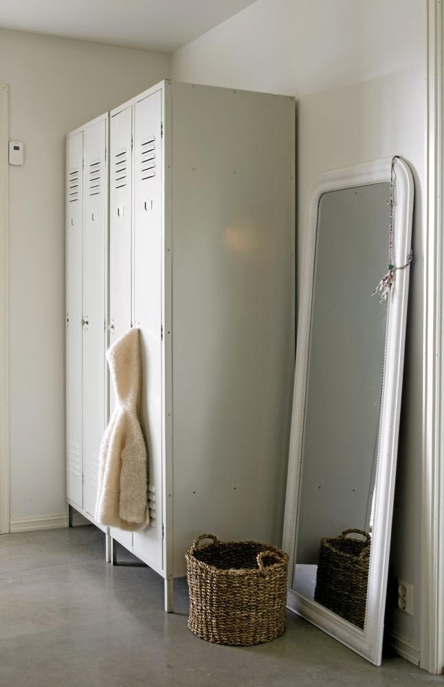 Gamle garderobeskap setter et røfft preg på entreen. Et stor speil er plassert på gulvet, lent mot veggen. Dette får den som speiler seg til å se lengre ut.