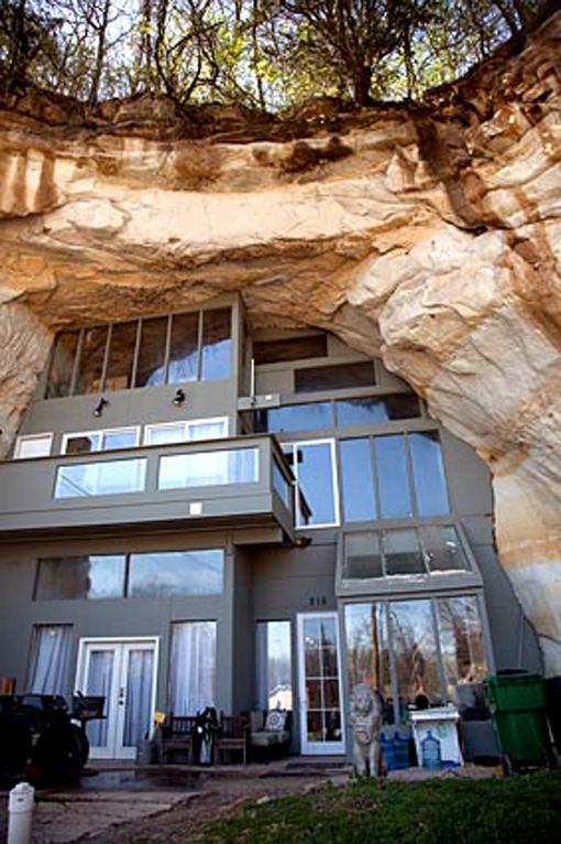 a modern metal house built into a rock cave ampitheater ... materials and spaces juxtaposed ...