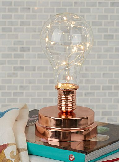 A modern lantern in this season's Scandinavian Comfort style   Garland of LED lights built into a transparent bulb mounted on a chic copper metal base   Batteries not included
