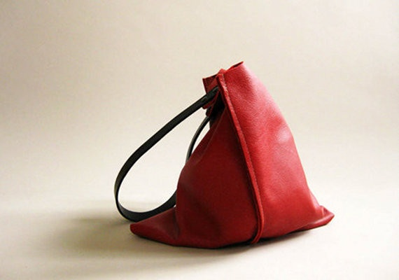 Available in two sizes, this sleek, unlined shoulder bag is crafted from soft, vibrant red leather with medium length black leather straps. The bag is finished with double screws and an interior keyring.  From Fog + Foundry. $165