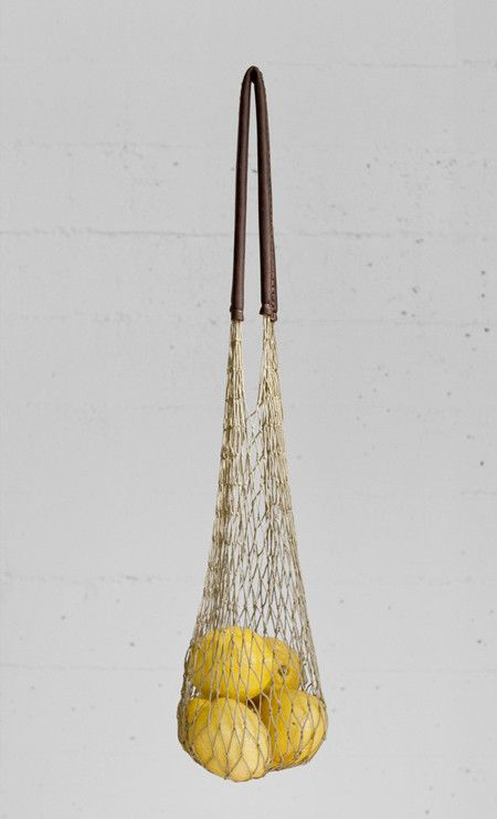 """AND SO IT GOES Natural net bag Made of natural colored cotton cord and soft brown leather handles.  Approximately 16"""" long with a 9"""" handle drop.  All bags are one of a kind, handcrafted knot by knot in Los Angeles. A percentage of each bag sold goes to The Clean Ocean Project."""