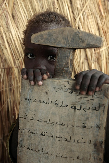A little girl from Sudan's Darfur is hiding behind her traditional slate after a coranic class in Arabic in a Birao's district, Vakaga prefecture, north-eastern Central African Republic. // credits: Pierre Holtz for UNICEF