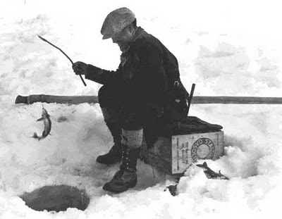 "Ice Fishing. ~ Not sure where this photo was taken, but this is a good historic take on what we call ""bucket fishing"". Islanders look forward to sunny, calm days when you can drill or chop a hole & drop a line. Modern times mean we use an auger, jig pole & a 5 gallon bucket! The pole laying in background was probably what this fisherman used to chop his hole."