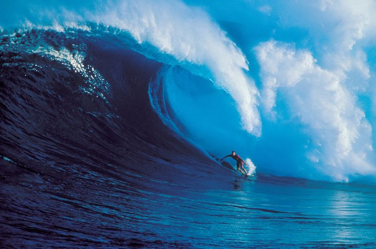 Buzzy Kerbox surfs a huge wave crashing behind Peahi on Maui, a surf break also known as Jaws.