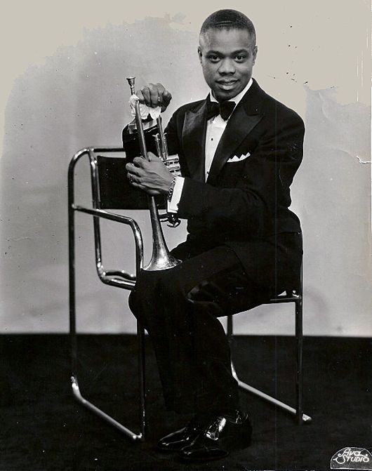 A Young Louis Armstrong Sitting On A Chair By Bruno Pollak