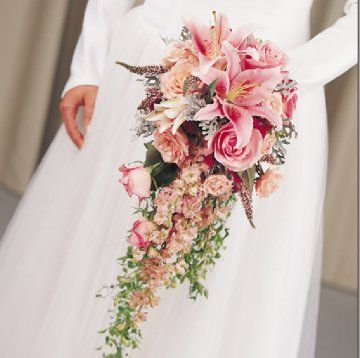 Pink larkspur, lilies, roses and heather result in a fabulously feathery cascading bouquet