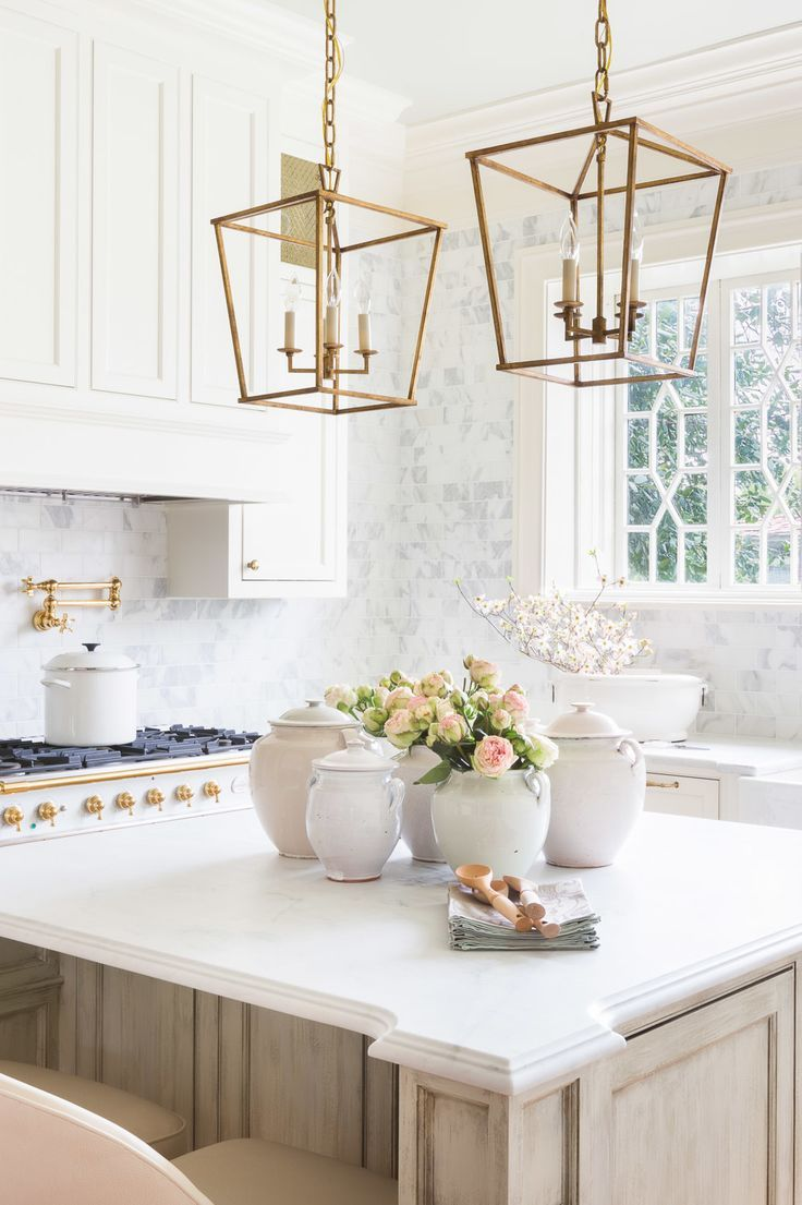 white kitchen, brass lanterns pendant lights, white and gold stove, marble tile wall ♥️