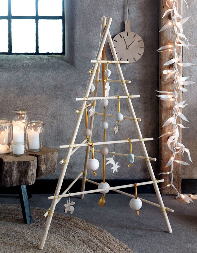 Houd je van een natuurlijke look? Met houten stokjes en elastiek knoop je vliegensvlug een kerstboom in elkaar. Lees op 101woonideeën hoe je dat doet.