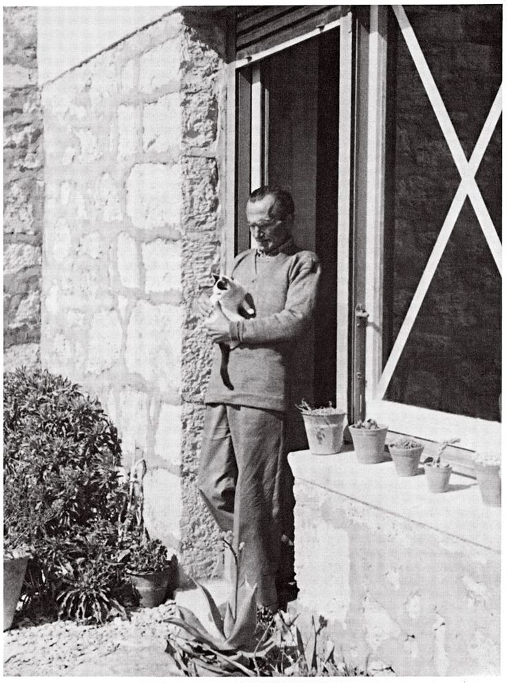 Nikos Kazantzakis at his house in Aegina with his cat Sminthitsa. March 1943.