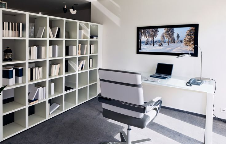 White and grey home office with small computer desk, contemporary white and grey desk chair. Bookshelves line one wall. Mounted flat screen television screen in front of the desk