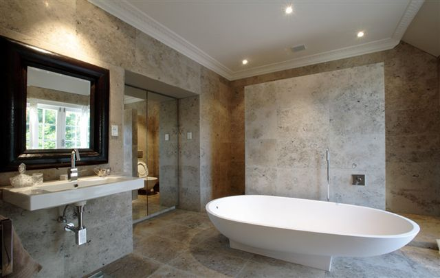 Very large pieces of Jura Grey Limestone on floor and walls. I love the freestanding tub here as well.