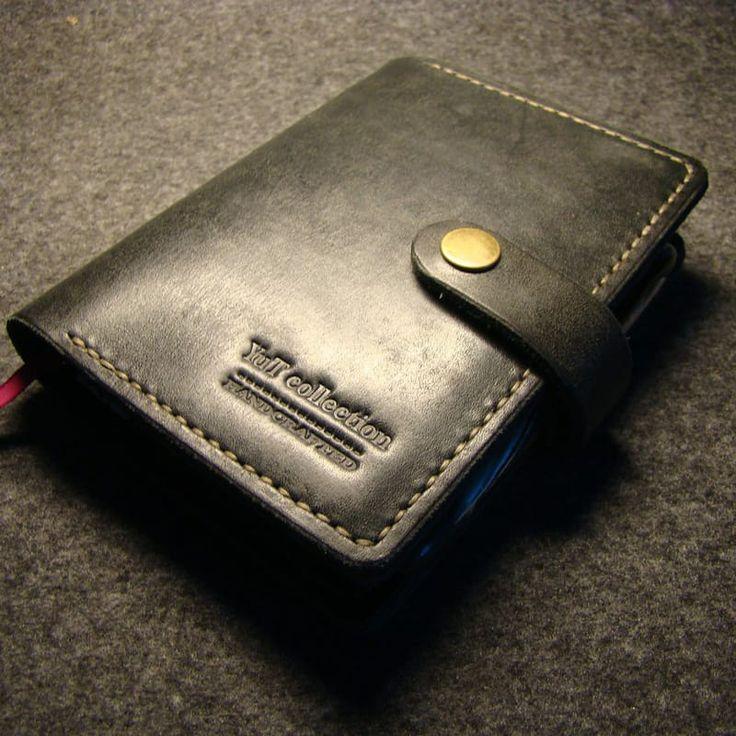 Небольшой черный кожаный брендовый блокнот YuT collection с заменяемым блокнотом, двумя отделениями для бумаг, шестью слотами для карт, кольцом-держателем для ручки и кнопокой-застёжкой. Блокнот изготовлен и прошит мастером вручную, на обложке вытеснен логотип с именем YuT collection. Практичный и б
