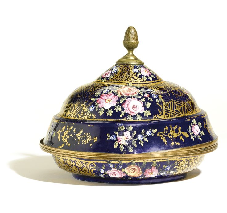 AN OTTOMAN SULEYMANIYE-WARE ENAMELLED DISH AND COVER (SAHAN), LATE 18TH CENTURY the shallow rounded dish with everted rim and a stepped domed cover surmounted by a foliate bud finial, decorated in overglaze enamels with a blue background and gilding with floral sprays interspersed with a diamond trellis  20.8cm. diam.