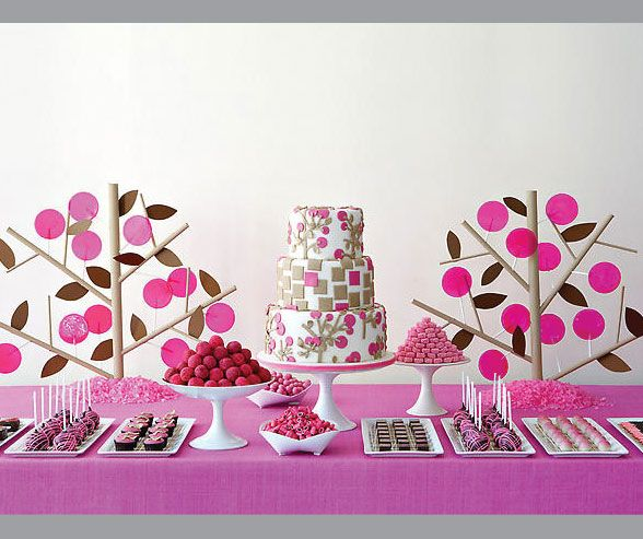 Candies and cupcakes in light and hot pink match the fondant decorations on this modern wedding cake.