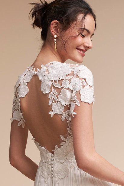 15 Beautiful Backless Wedding Dresses & Gowns You Need to See: An illusion bodice with graphic floral appliqué and fluttery cap sleeves. http://www.confettidaydreams.com/15-beautiful-backless-wedding-dresses-gowns/